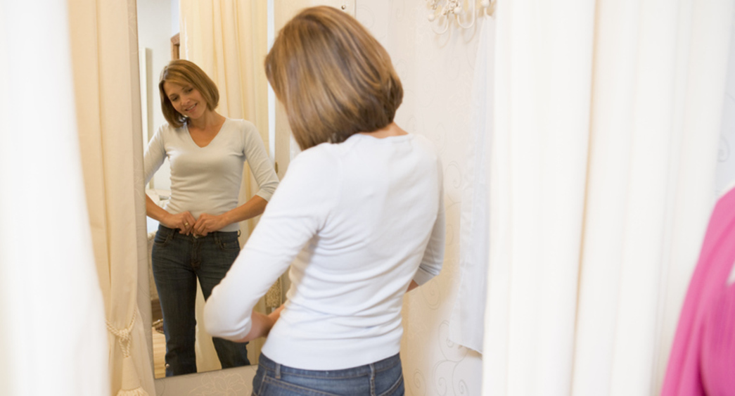 Woman looking at reflection in dressing room mirror