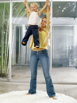 Woman lifting toddler high in the air