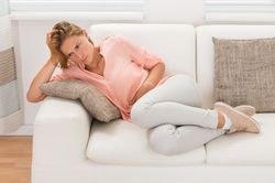Woman sitting on couch with stomach pain