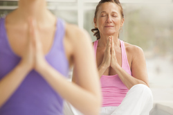 Middle aged woman in yoga, prayer-like pose